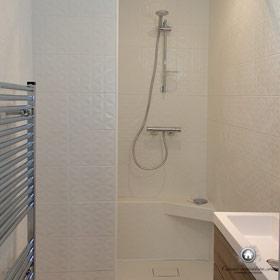 salle de bain avec un coin douche et au premier plan la vasque